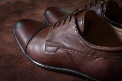Scarpe degli uomini del cuoio di Brown su fondo di cuoio Immagini Stock Libere da Diritti
