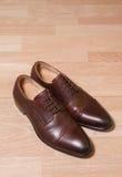 Scarpe degli uomini del cuoio di Brown su terra di legno Fotografia Stock