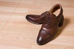 Scarpe degli uomini del cuoio di Brown su terra di legno Immagine Stock