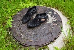 Scarpe del ` s degli uomini anziani Abbandonato sulla via dopo una pioggia Consumato e Fotografia Stock Libera da Diritti