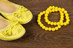 Scarpe del ` s delle donne e disposizione gialla del piano delle perle Immagini Stock