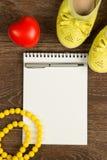 Scarpe del ` s delle donne, perle gialle, penna e disposizione bianca del piano del taccuino Immagini Stock Libere da Diritti