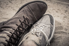 Scarpe dell'uomo e della donna che si trovano accanto a ogni altro sulla sabbia Fotografie Stock Libere da Diritti