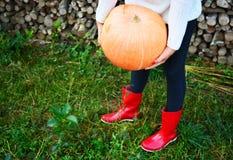 Scarpe della pioggia della zucca di autunno e di legno rossi con il fondo dei leavs Fotografie Stock Libere da Diritti