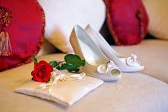 Scarpe della sposa e di un cuscino con gli anelli e la rosa rossa immagini stock libere da diritti