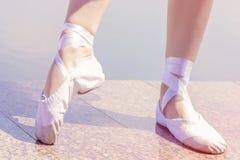 Scarpe di balletto per ballare calzate sulle loro ragazze del ballerino dei piedi fotografia stock libera da diritti