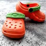 Scarpe di bambino arancio e pavimento grigio Fotografie Stock Libere da Diritti