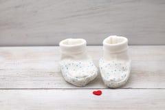 Scarpe di bambino bianche su un fondo bianco e su un cuore rosso Immagini Stock