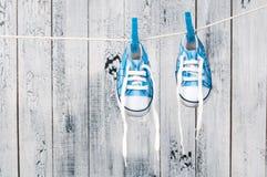 Scarpe di bambino che appendono sulla corda da bucato. Fotografia Stock