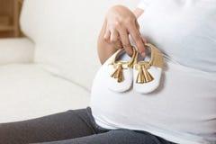 Scarpe di bambino felici della tenuta della mano della donna incinta mentre sedendosi sul gr Immagini Stock Libere da Diritti