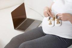 Scarpe di bambino felici della tenuta della mano della donna incinta mentre sedendosi sul gr Immagine Stock