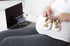 Scarpe di bambino felici della tenuta della mano della donna incinta mentre sedendosi sul gr Immagini Stock