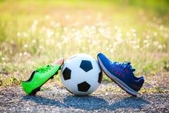 Scarpe di calcio e di calcio con confuso di erba verde per addestramento del calciatore immagini stock