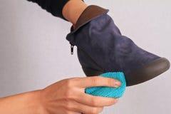 Scarpe di cuoio del camoscio di pulizia della donna La pelle scamosciata calza la cura di inverno Fotografie Stock