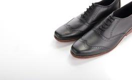 Scarpe di cuoio nere brillanti su copyspace bianco immagini stock