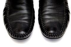 Scarpe di cuoio nere degli uomini contro fondo bianco fotografia stock