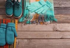 Scarpe di inverno, guanti, sciarpe su vecchio fondo di legno Fotografia Stock
