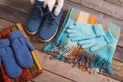 Scarpe di inverno, guanti, sciarpe su vecchio fondo di legno Immagini Stock