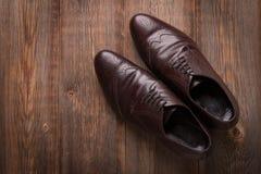 Scarpe di marrone del ` s degli uomini su un fondo di legno Immagine Stock