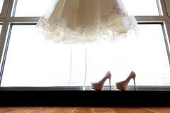 Scarpe di nozze e del vestito da sposa Fotografie Stock