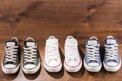 Scarpe di palestra multicolori della gioventù sul pavimento Fotografia Stock