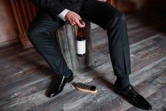 Scarpe di pulizia su fondo di legno scarpa nera con una spazzola Chiave inglese rossa Anelli di cerimonia nuziale Bottiglia da bi Immagine Stock