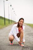 Scarpe di sport dell'allacciamento della donna prima di correre Immagine Stock
