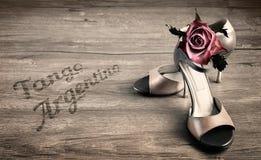 Scarpe di tango dell'Argentina e una rosa su un pavimento di legno immagine stock libera da diritti