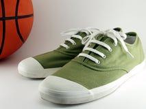 Scarpe di tela verdi con pallacanestro Immagini Stock Libere da Diritti