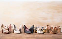 Scarpe differenti del ` s della donna sul pavimento di legno Fotografia Stock