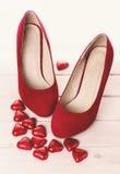 Scarpe e cuori rossi del cioccolato per il biglietto di S. Valentino Fotografie Stock Libere da Diritti
