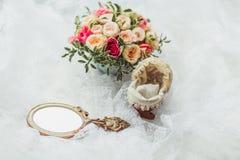 Scarpe e gioiello di lusso della sposa sul sofà Immagini Stock