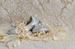 Scarpe e perle di bambino sul fazzoletto del pizzo Immagini Stock
