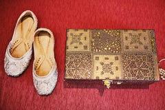 Scarpe e scatola bianche dell'oro di braccialetti su fondo rosso Fotografia Stock Libera da Diritti