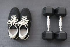 Scarpe e teste di legno sulla stuoia di yoga Fotografia Stock