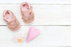 Scarpe e un rosa della tettarella per una neonata su una parte posteriore di legno di bianco Immagine Stock
