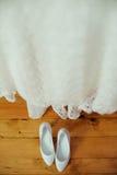 Scarpe e vestito bianchi di nozze sui precedenti di legno Fotografie Stock