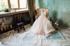 Scarpe e vestito da sposa sulla sedia nella sala Immagine Stock