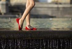Scarpe ed acqua rosse Fotografie Stock