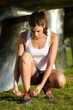 Scarpe femminili di sport dell'allacciamento del corridore prima di correre fotografia stock