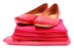 Scarpe femminili e mucchio dei vestiti rossi Priorità bassa bianca Immagine Stock