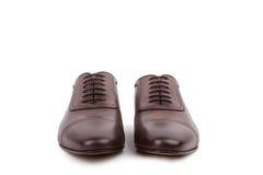 Scarpe maschii sui precedenti bianchi Fotografia Stock
