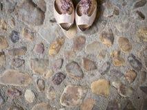 Scarpe nuziali su terra lapidata fotografia stock