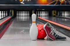 Scarpe, perno di bowling e palla per il gioco lanciante Fotografia Stock