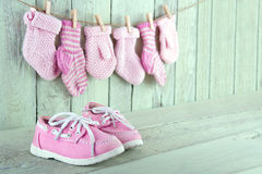 Scarpe rosa del bambino su fondo verde chiaro di legno fotografia stock