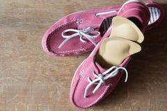Scarpe rosa di sport con i sottopiedi ortopedici Paia delle scarpe da tennis sopra Fotografia Stock