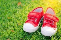 Scarpe rosse per i bambini sul pavimento dell'erba verde Fotografie Stock Libere da Diritti