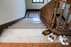 3 scarpe si avvicinano alla scala di legno Fotografia Stock