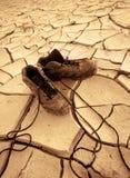 Scarpe su una terra asciutta e calda nel mittle di in nessun posto Fotografie Stock
