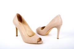 Scarpe a tacco alto del ` elegante beige delle signore su un fondo bianco Fotografia Stock